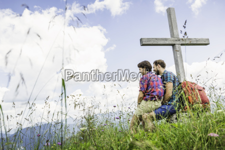 young couple sitting by cross tyrol