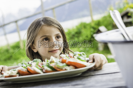 young girl holding salad plate for