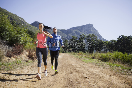 young couple jogging in forest