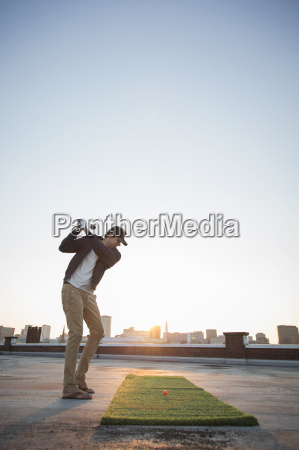 man playing golf on rooftop