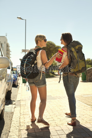 two female backpackers with map cape