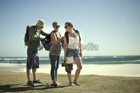 young friends checking backpacks on beach