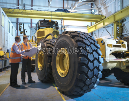 engineers with engineering drawings inspecting heavy
