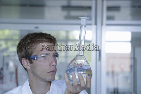 young male scientist holding up volumetric