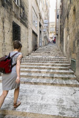 female tourist walking up stairs valletta