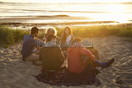 adult friends picnicing at sunset on