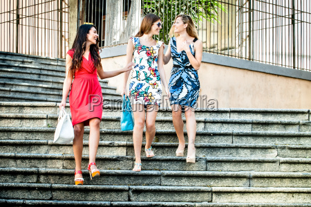 three fashionable young women chatting on