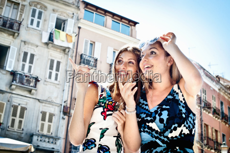 two young female friends pointing and