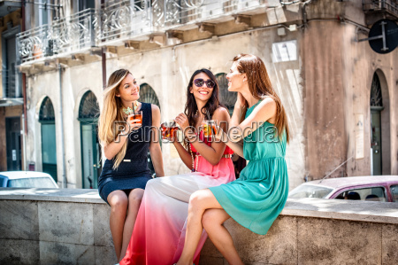 three young fashionable female friends having