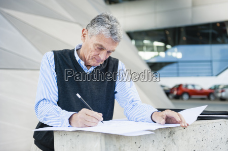 senior adult businessman making notes on