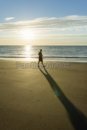 mid adult woman strolling on beach