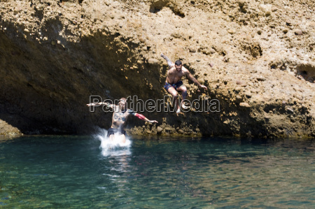 two young men jumping into sea