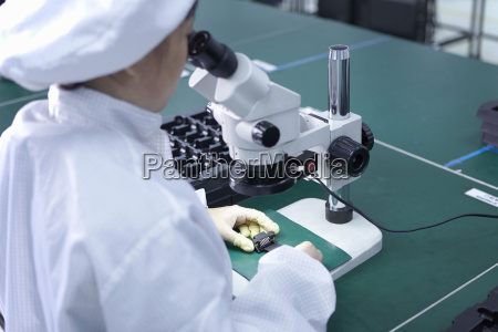 worker using microscope in factory that