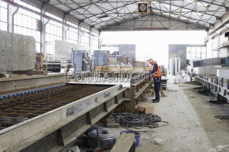 fabrikarbeiter an der produktionslinie in derbetonbewehrungsfabrik