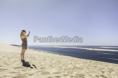young woman photographing sea with smartphone
