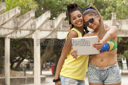women taking selfie using digital tablet