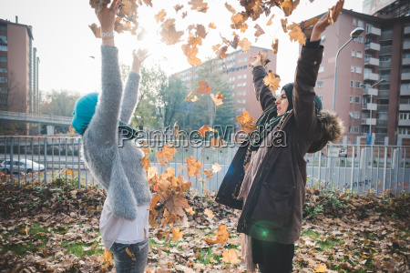two young women throwing autumn leaves