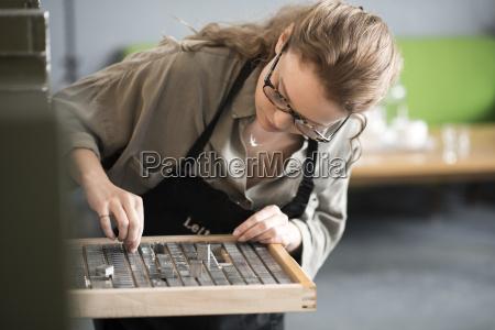 woman choosing letterpress from tray in