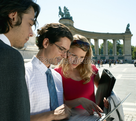 three businesspeople looking at laptop