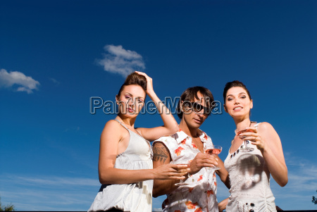 three people with drinks outdoors
