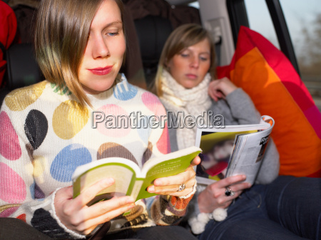 young women reading in car