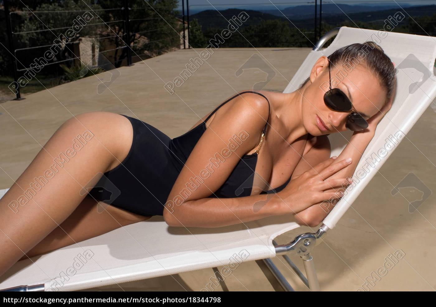 woman, sunbathing, by, a, swimming, pool - 18344798
