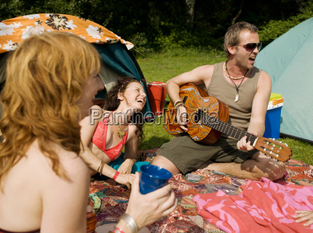 three people singing together at camp