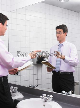 man practicing speech in office washroom