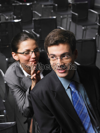 woman whispering to man sitting in