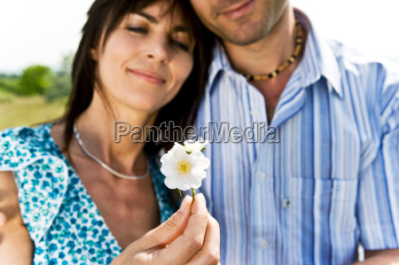 man and woman holding flower