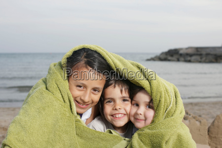 three young children in towel on