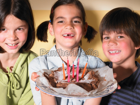 children holding a birthday cake