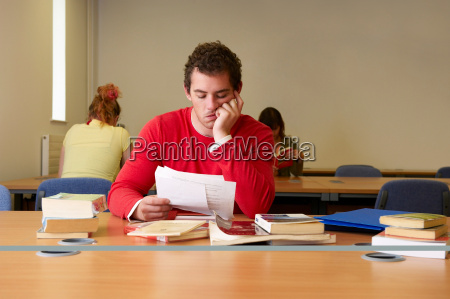 bored young man seated at desk
