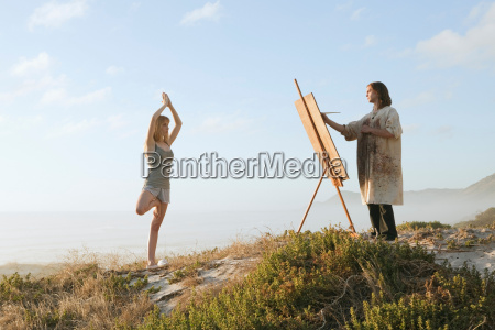 young man painting girl in landscape