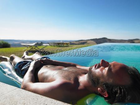 man, resting, in, swimming, pool - 18348538