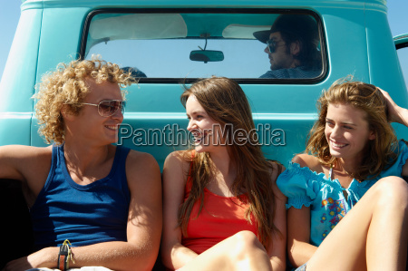 young people traveling in pickup truck
