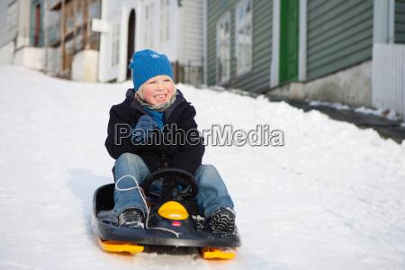 scandinavian boy on a sled