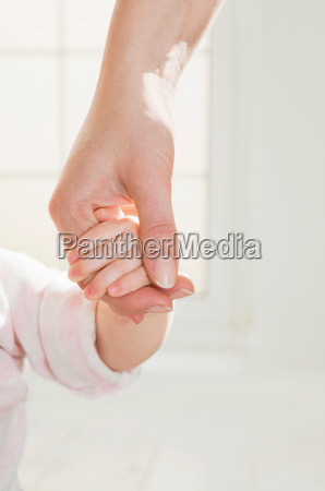 a mothers hand holding her babys