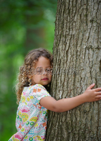 young girl hugging tree eyes closed