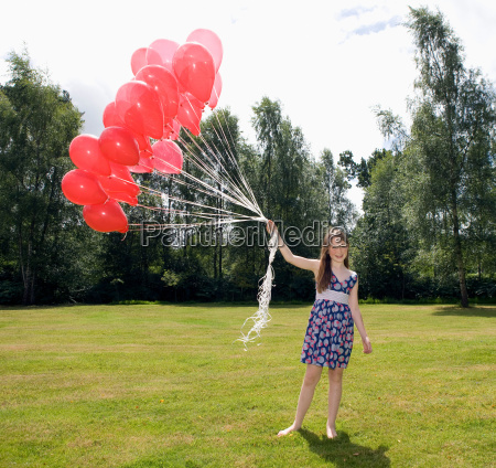 girl holding bunch of red balloons