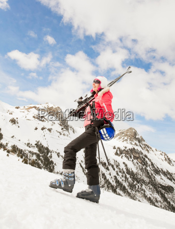 woman walking in snow with skis