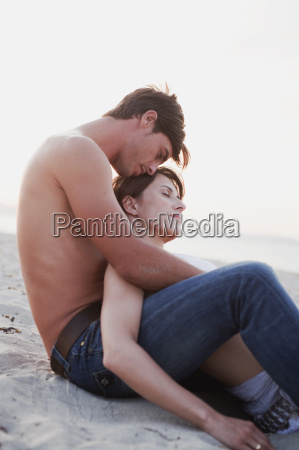 couple embracing sitting on the beach