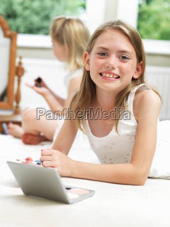 girl smiling putting on make up