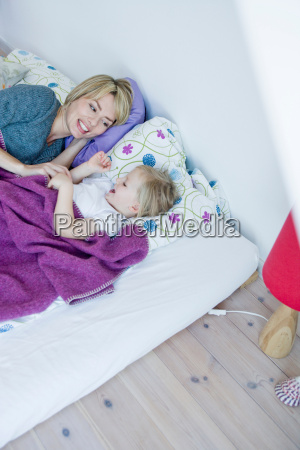 girl and woman lying in bed