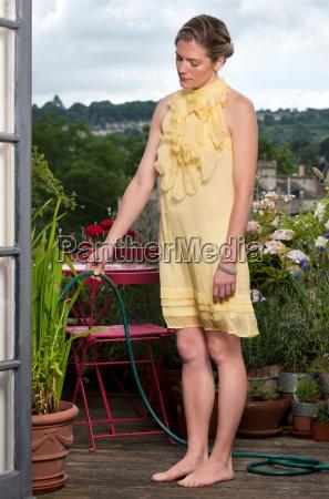 woman watering plants on balcony