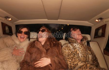three women on backseat of luxury