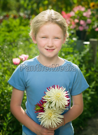 a young girl holding some flowers