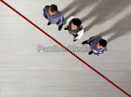 business men standing by red line