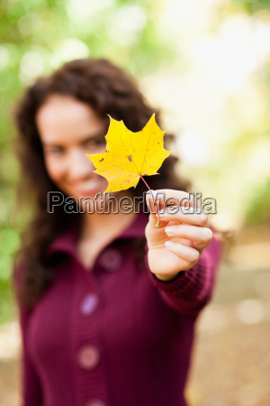 young woman shows leaf