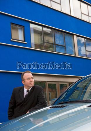 businessman chauffeur leaning on car